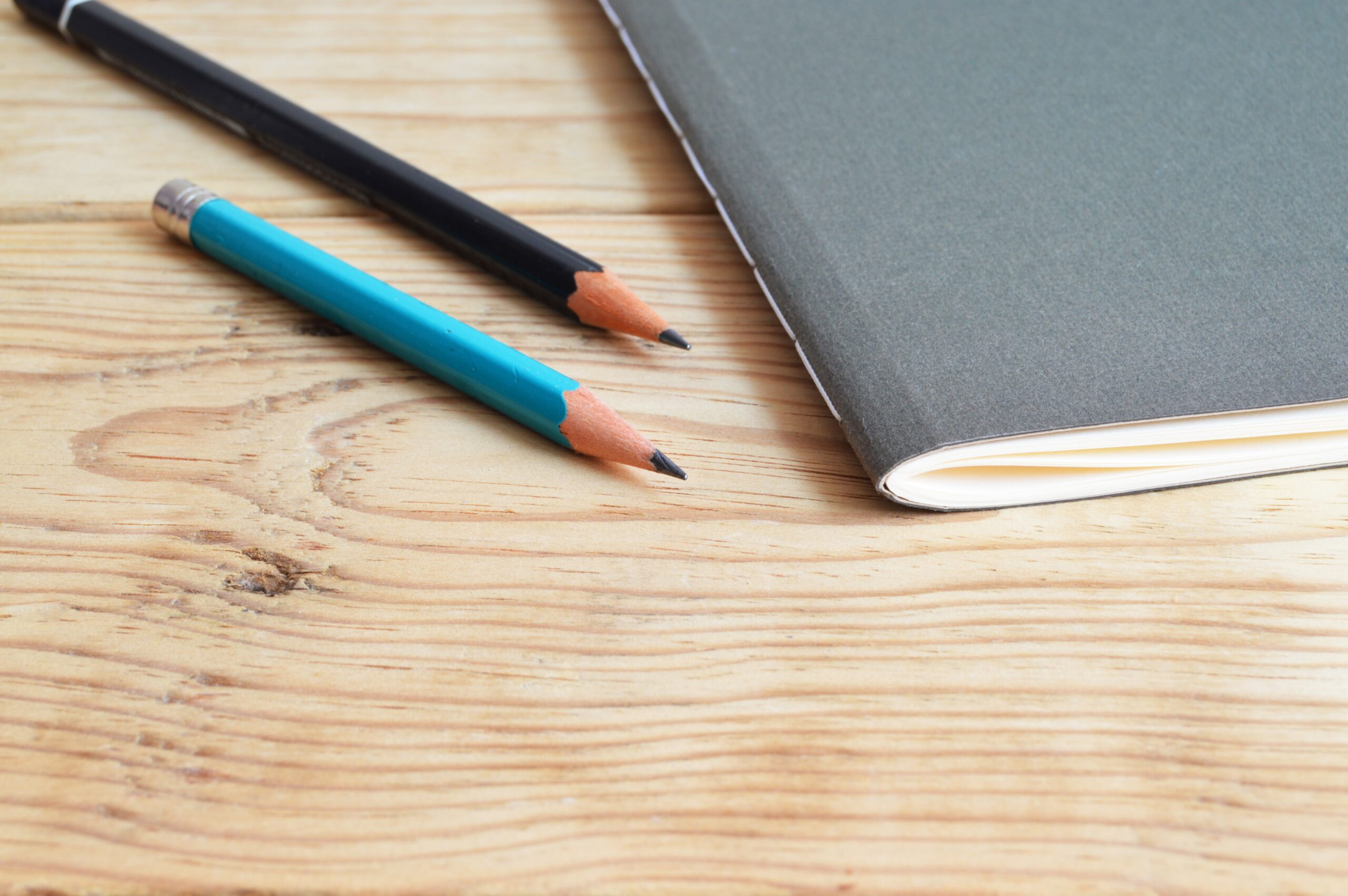 Black notebook with 2 pencils on wooden surface