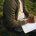 Person sitting on grass writing on paper