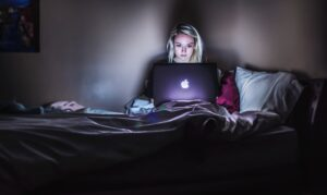 A person on their bed with a laptop