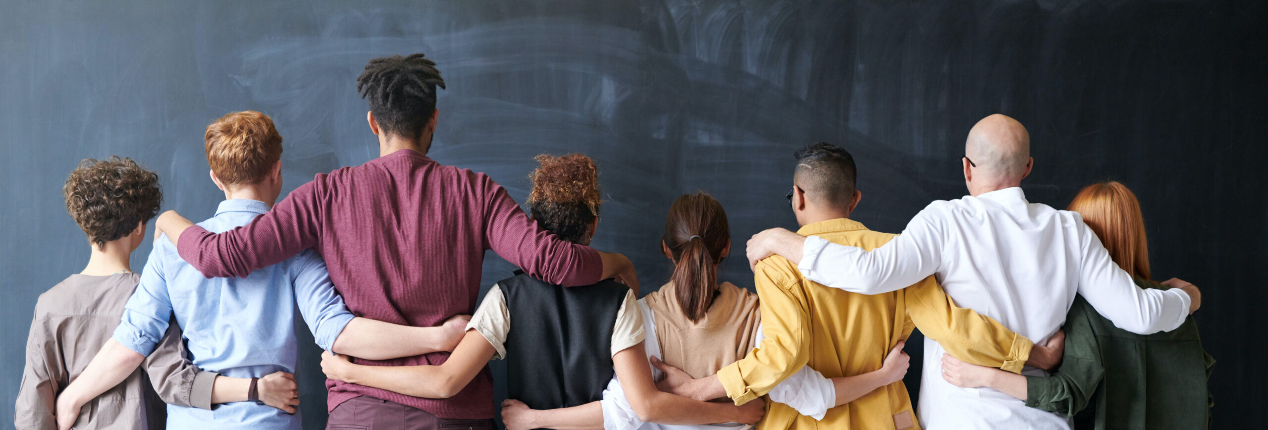 People facing a chalkboard with arms around each other's shoulders