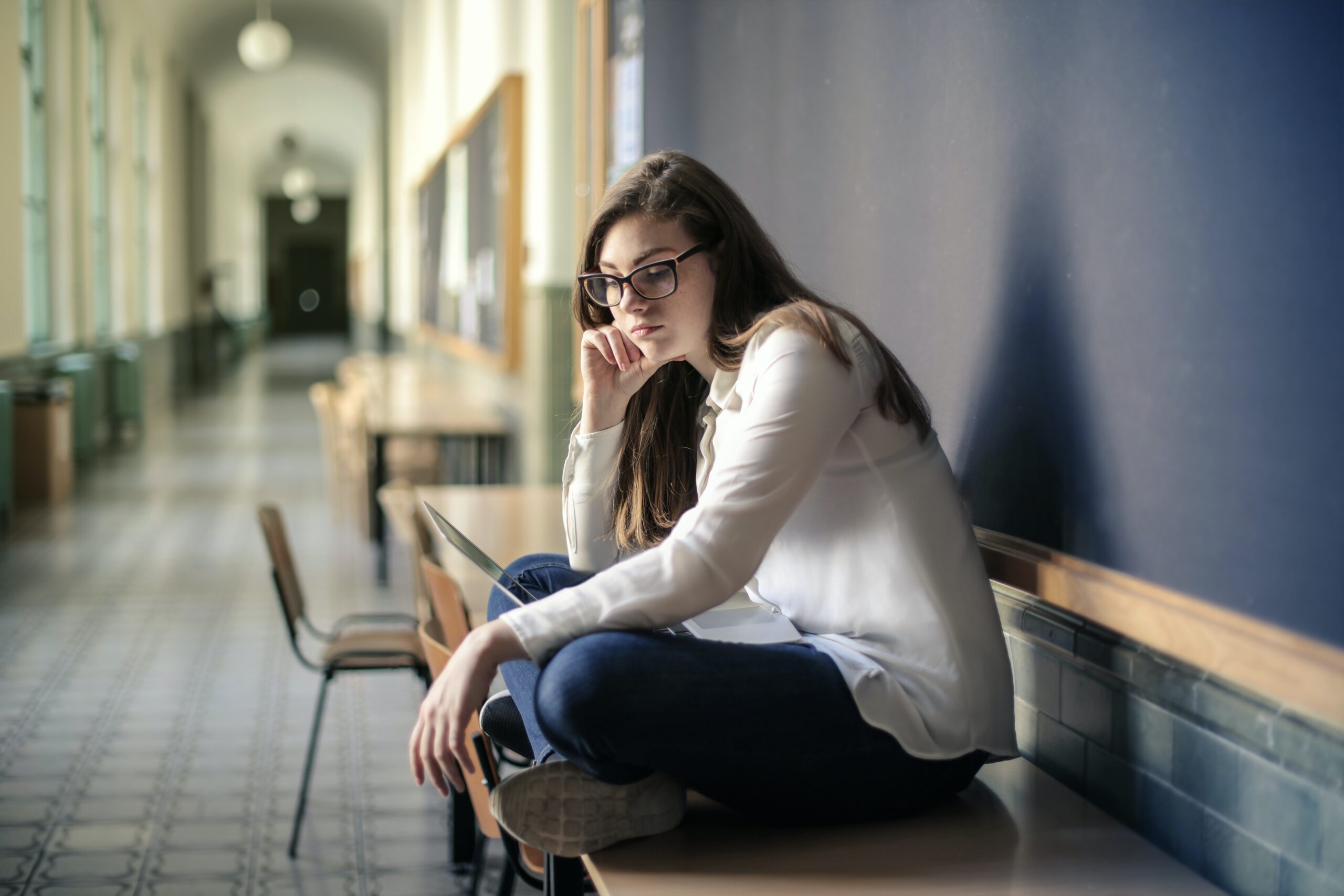 sad person sitting alone on bench in school hallway