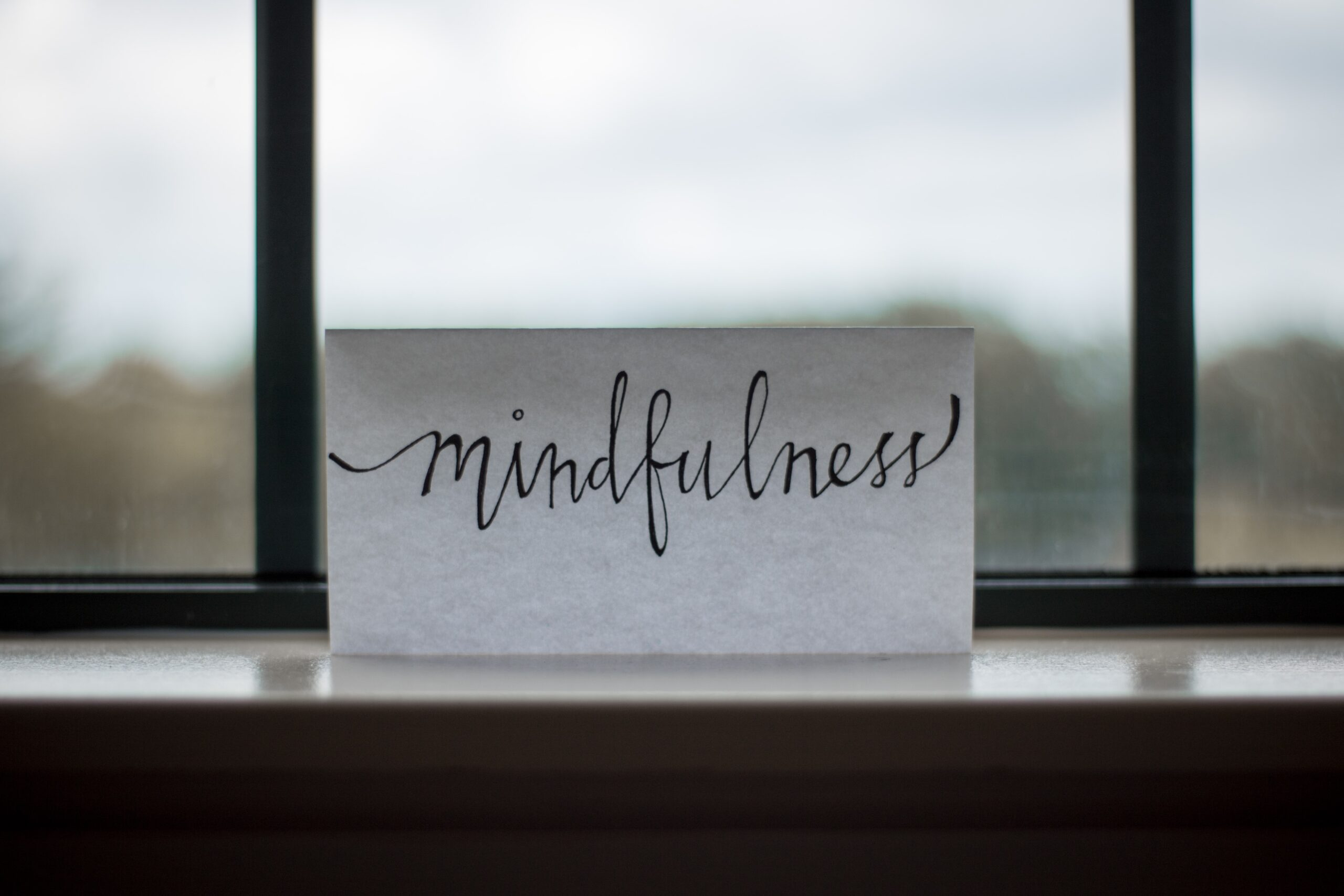 a white piece of paper propped up in a window with the word mindfulness hand written neatly on it