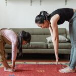 parent and child in exercise clothes reaching to touch their toes