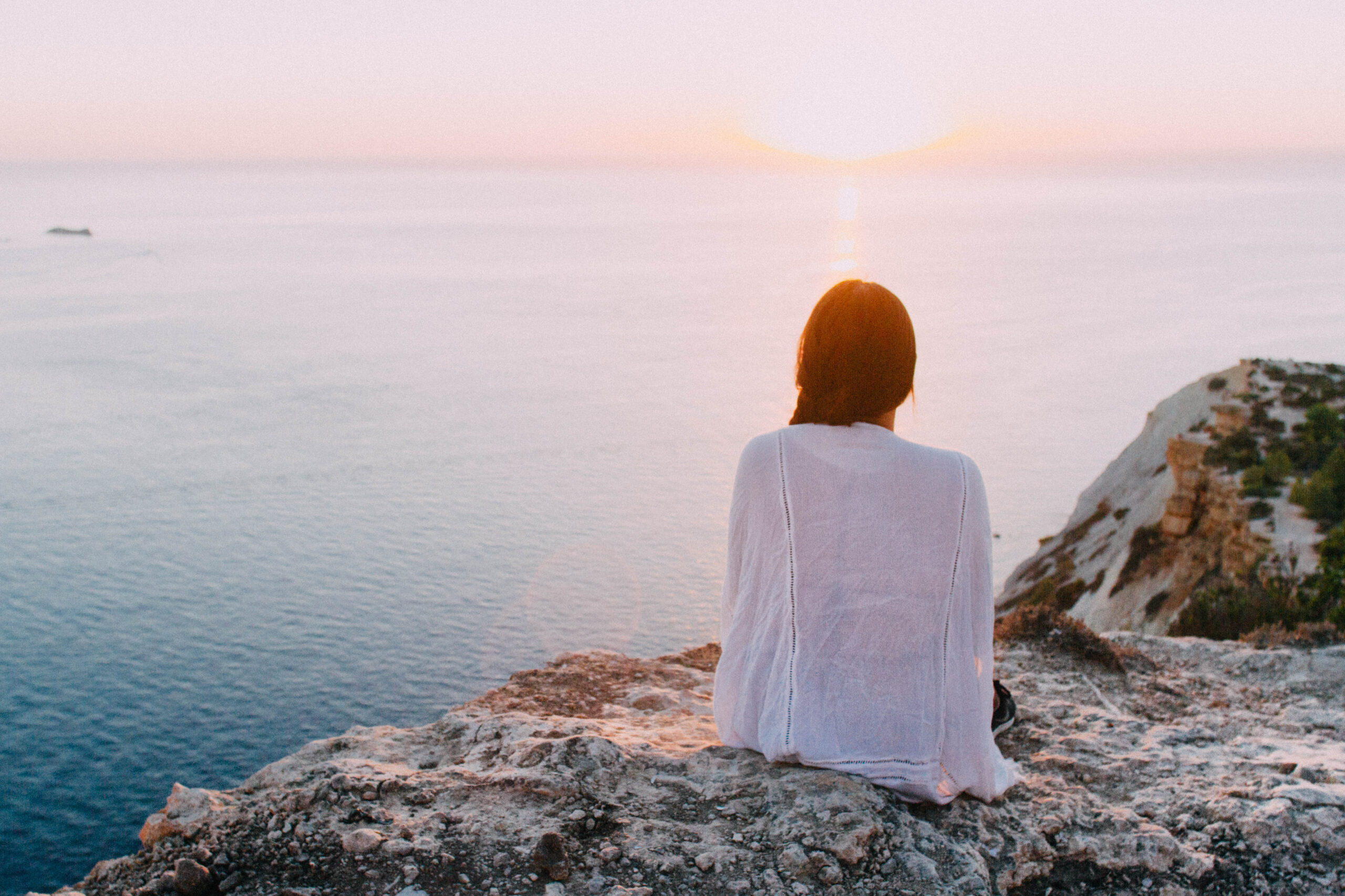 a person sitting on a cliff overlooking the ocean