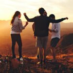 Four people dancing on a hilltop at sunset